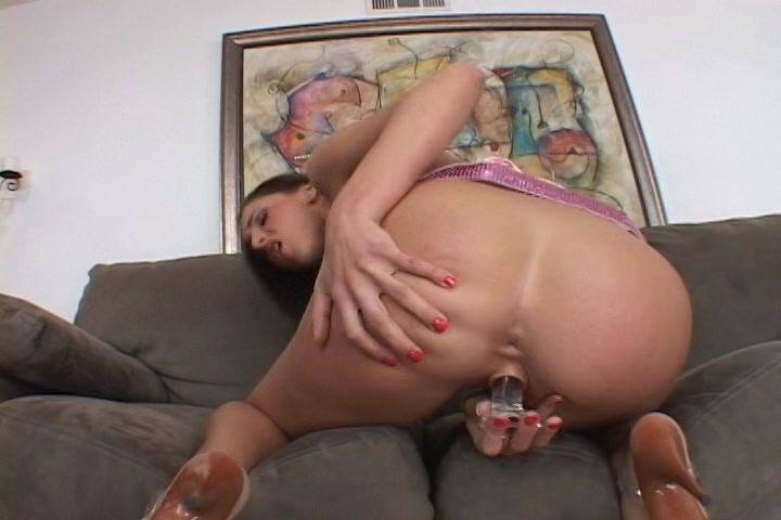 Ze laat de glazen sexspeeltje in en uit haar onbehaarde vulva glijden tot ze een orgasme ontvangst.