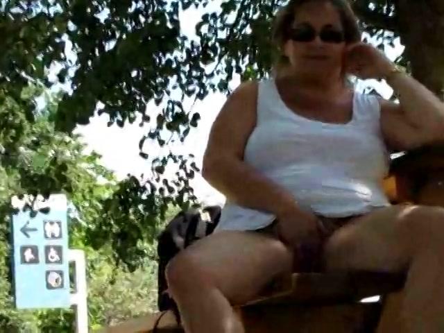 de brutale opwindende opoe heeft geen onderbroekje aan onder haar korte jurkje.  zij vingert haar poes in dat park te gelijkertijd opa filmt.