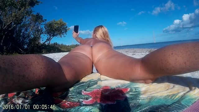 op het strand filmt dit witte grietje haar blote achterwerk