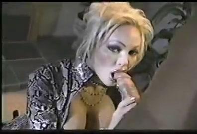 Wulps kijkend in de camera geeft de blondine zijn enorme pik een pijp beurt tot dat hij klaar komt en de teelvocht in haar gelaat spuit.