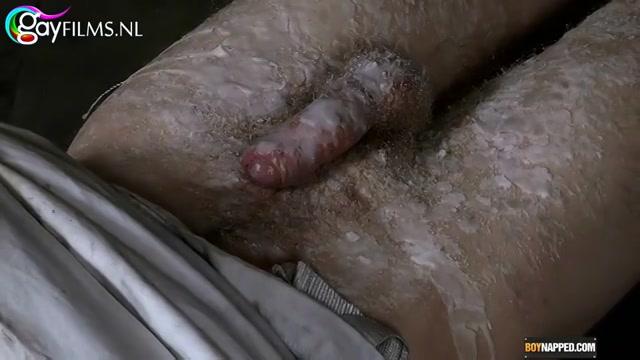Liggend in een dwangbuis word er hitsige kaarsvet over zijn ballen en piemel gegoten.