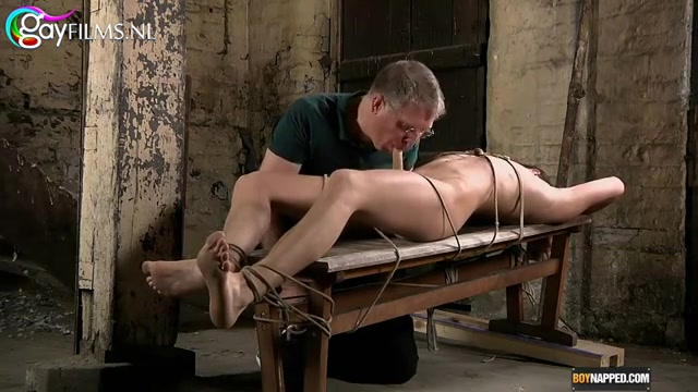 hij ligt vastgebonden en word gekieteld door de rijpe kennis die de knul ook een zuig beurt geeft.