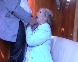 de oudere vrouw geeft zijn enorme pik een pijp beurt,  tot hij klaar komt en haar gelaat vol teelvocht spuit.
